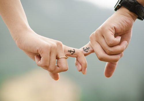 happy-couple-with-matching-tattoos-locking-fingers